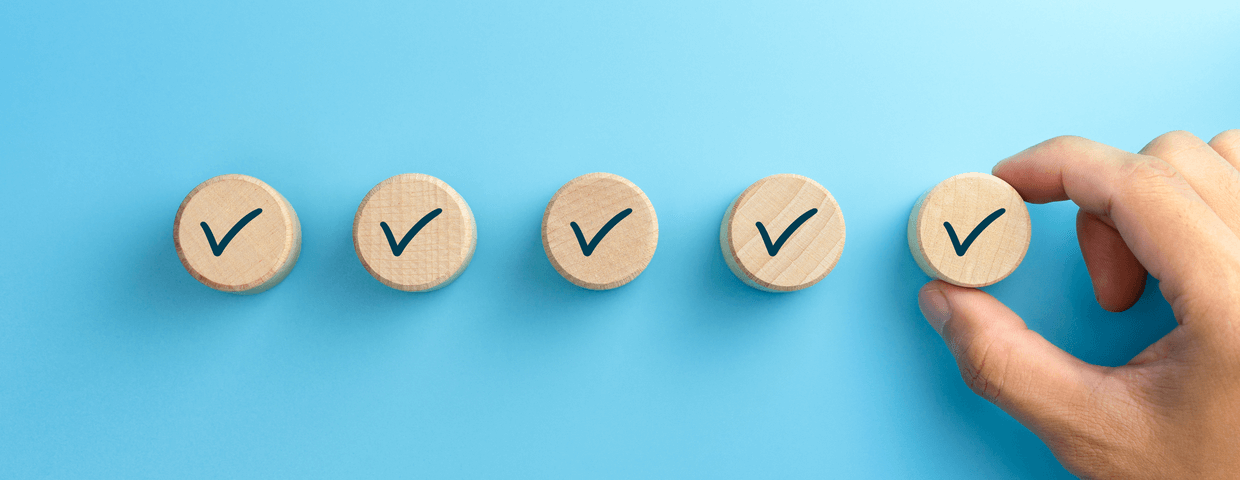Check mark on wooden blocks being placed down by hand on a blue background. Checklist concept.