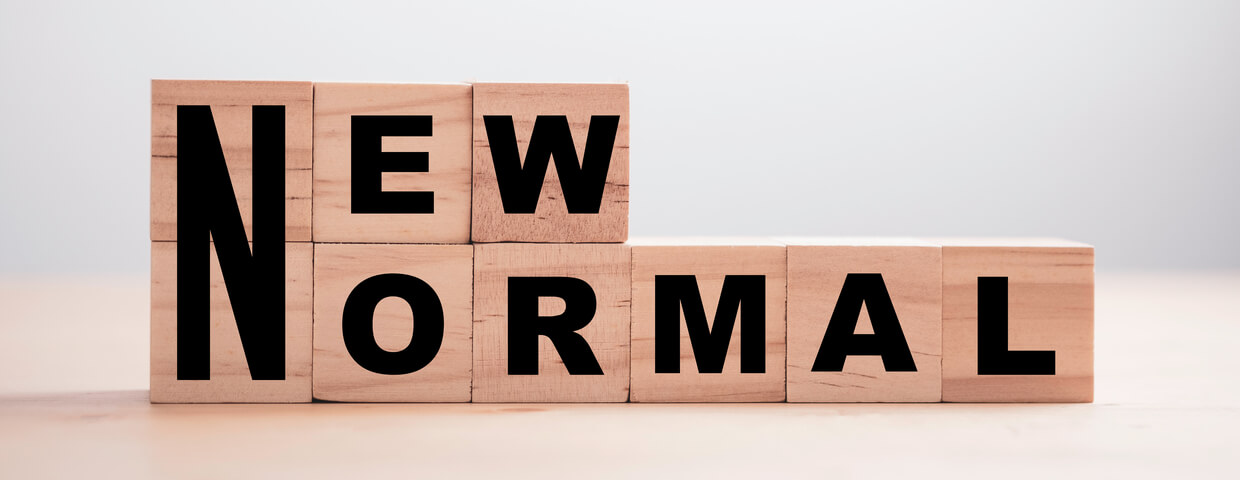 Wooden blocks stacked on top of each other with the words new normal