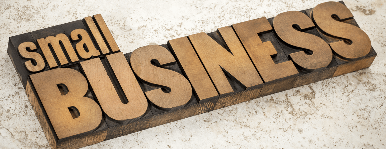wooden sign that says small business laying on table
