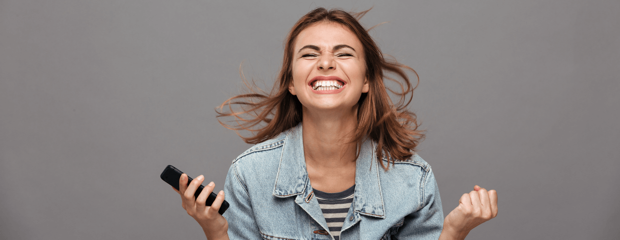 Close-up portrait of screaming young girl holding smartphone showing winner gesture, isolated on gray background