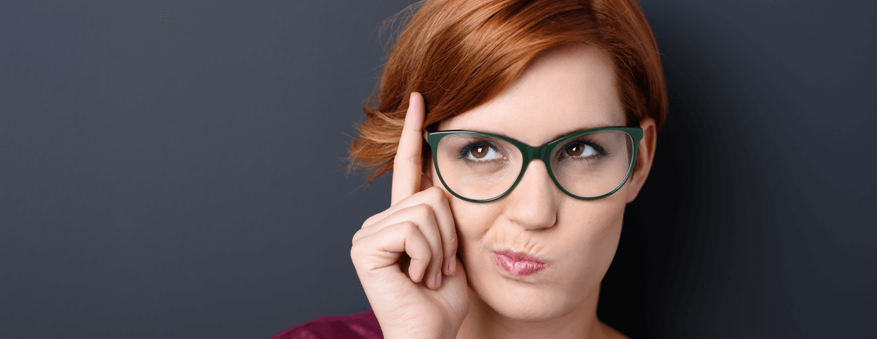 Woman with red hair and glasses putting a finger up to her temple with a quizzical look on her face