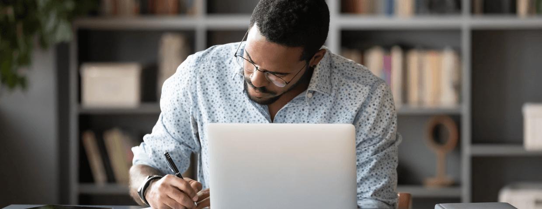 Man sitting with laptop, writing down something.