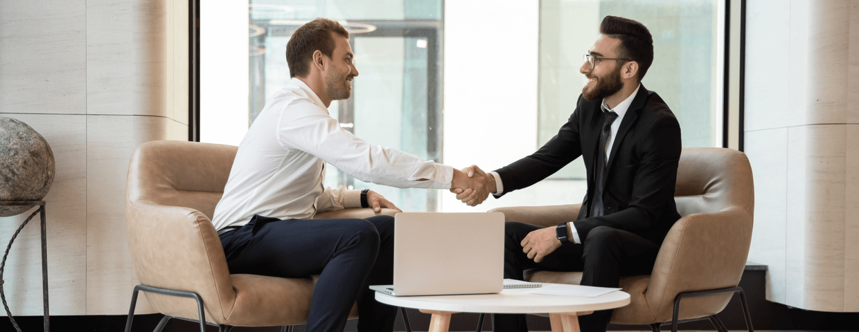 Two business men shaking hands while sitting.